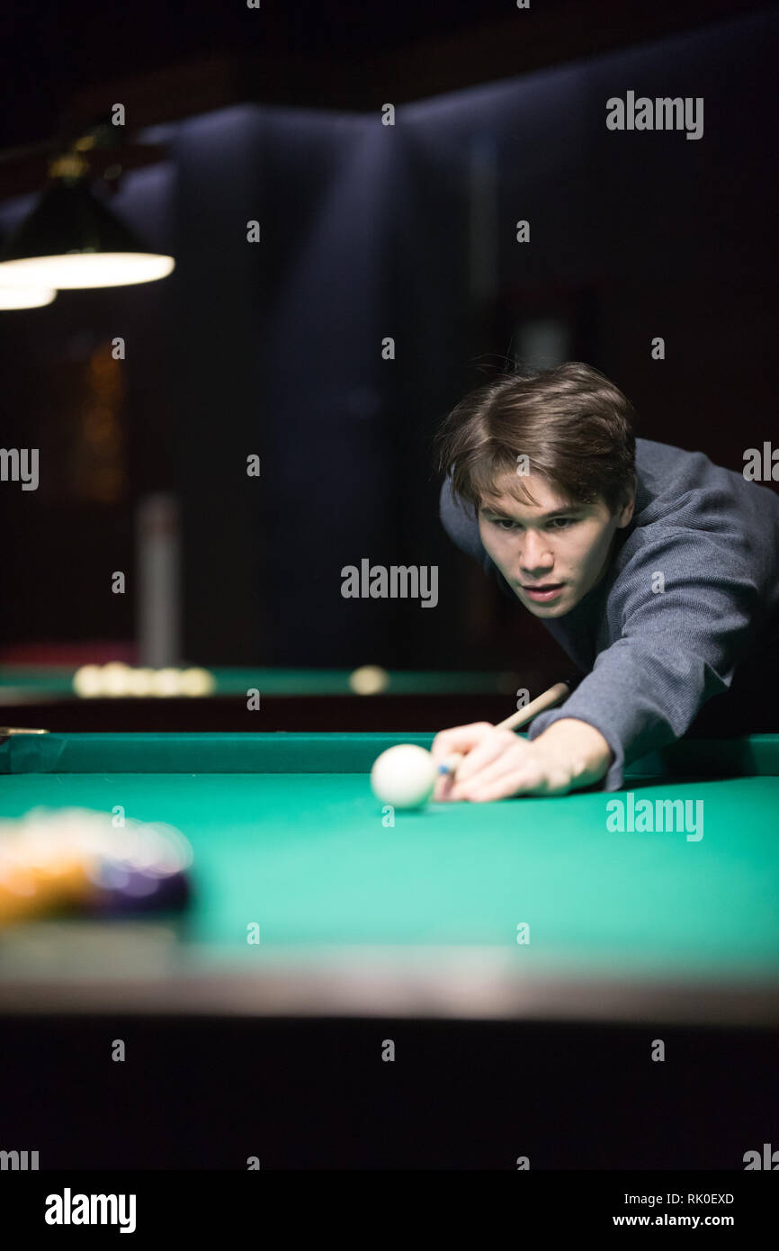 Entertainment concept. A young man playing billiard - Stock Image