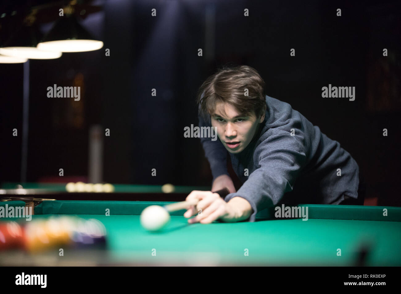 Entertainment concept. Concentrated young man playing billiard - Stock Image