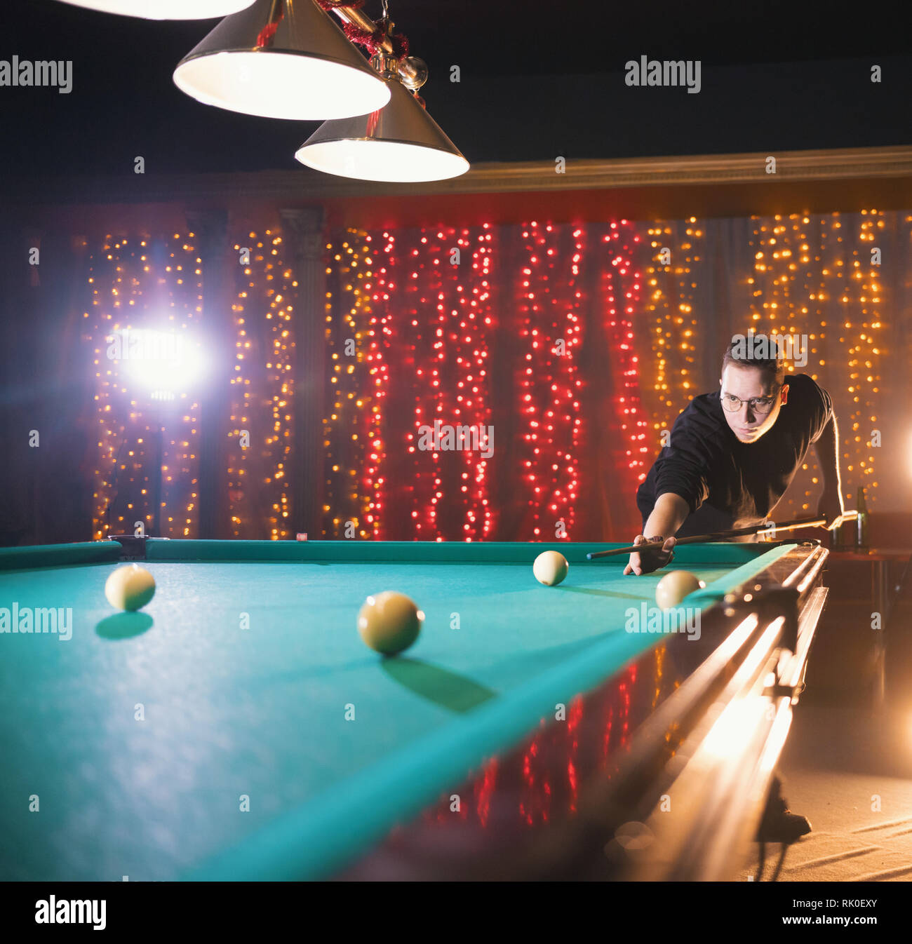 Entertainment concept. Young man in glasses playing billiard - Stock Image