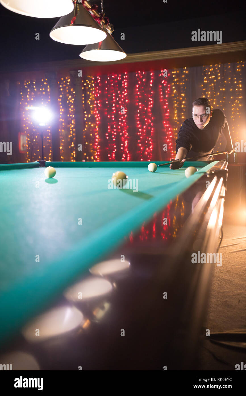Entertainment concept. Concentrated young man in glasses playing billiard. Perspective - Stock Image