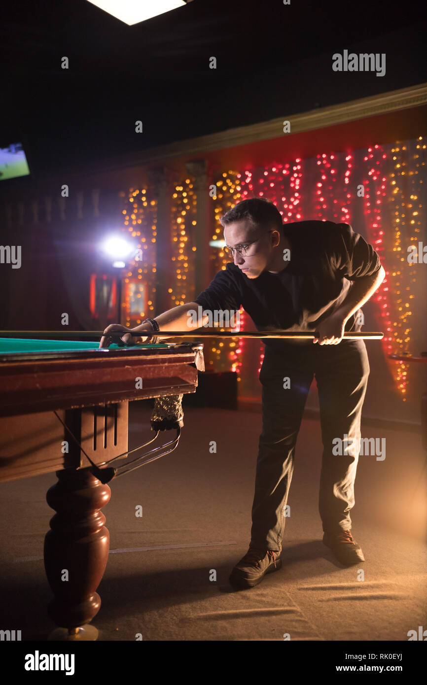 Entertainment concept. Young man in glasses playing billiard. Side view - Stock Image