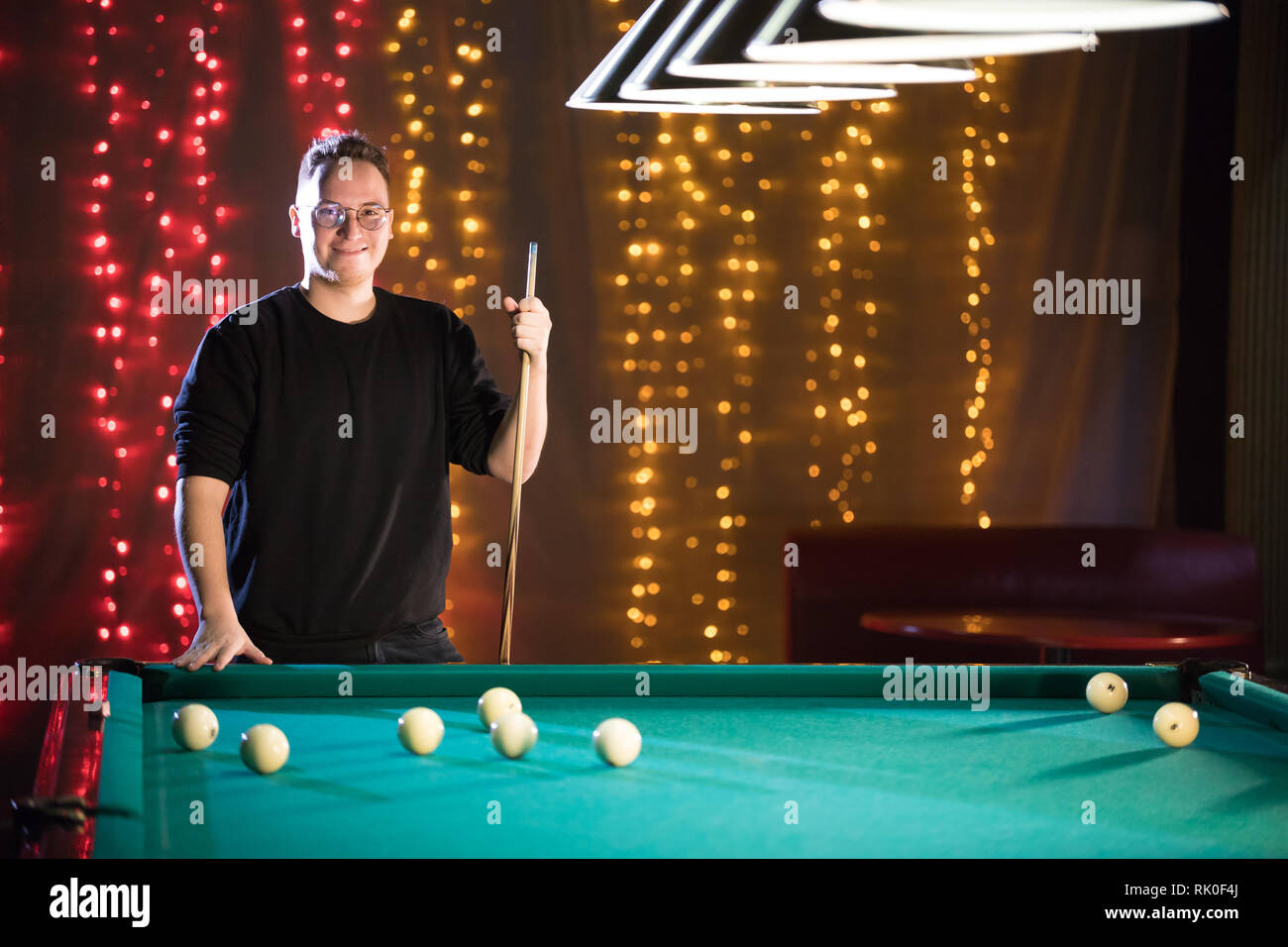 Billiard club. A young man in glasses standing by the table - Stock Image