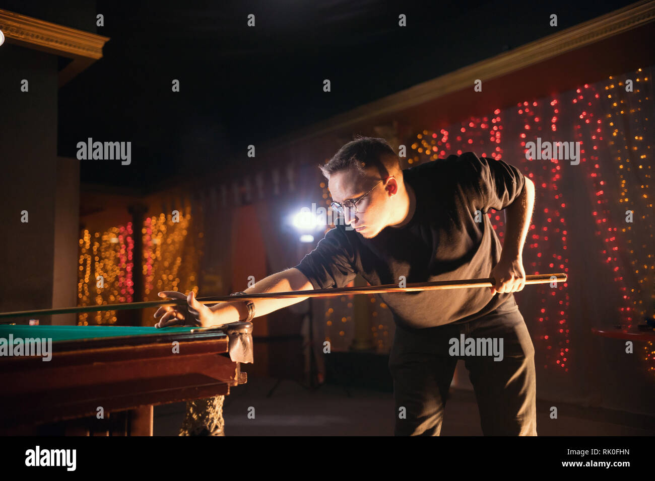 Entertainment concept. Concentrated young man in glasses playing billiard. Side view - Stock Image
