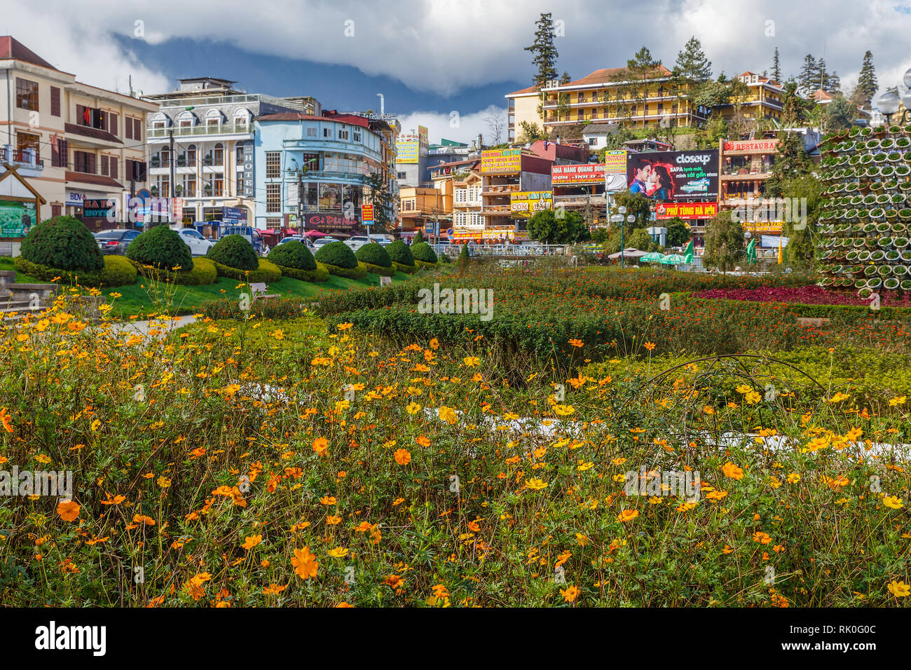 Sapa, Vietnam - November 20, 2018: View of the street of the city of Sapa from the park near the lake. Flower bed in the foreground. - Stock Image