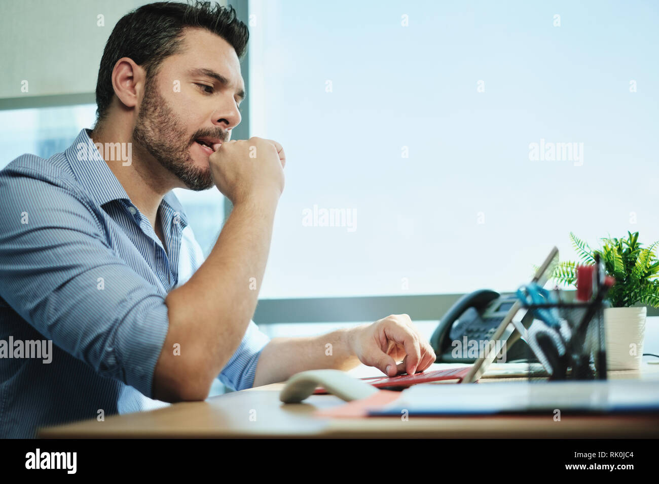 Anxious Businessman Biting Nails Working With Laptop Computer In Office - Stock Image