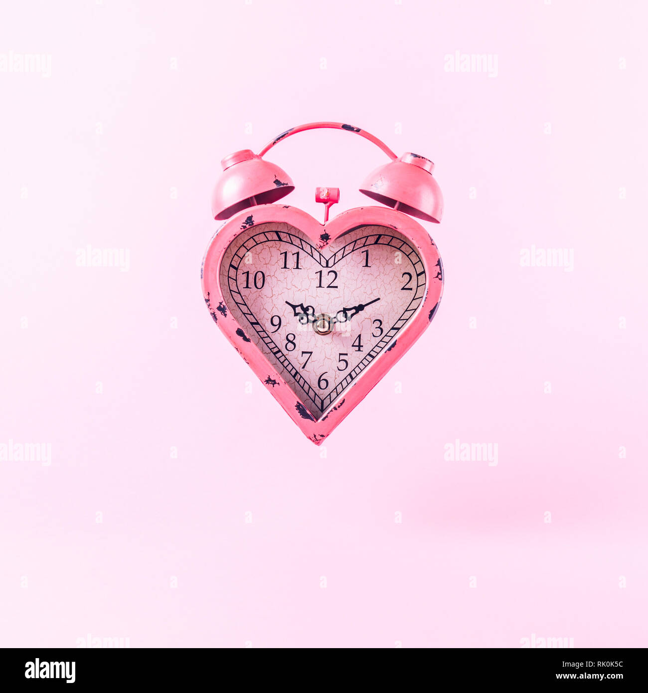 Heart shaped clock on pink background.  Valentines day and love infitity and duration concept. Square - Stock Image