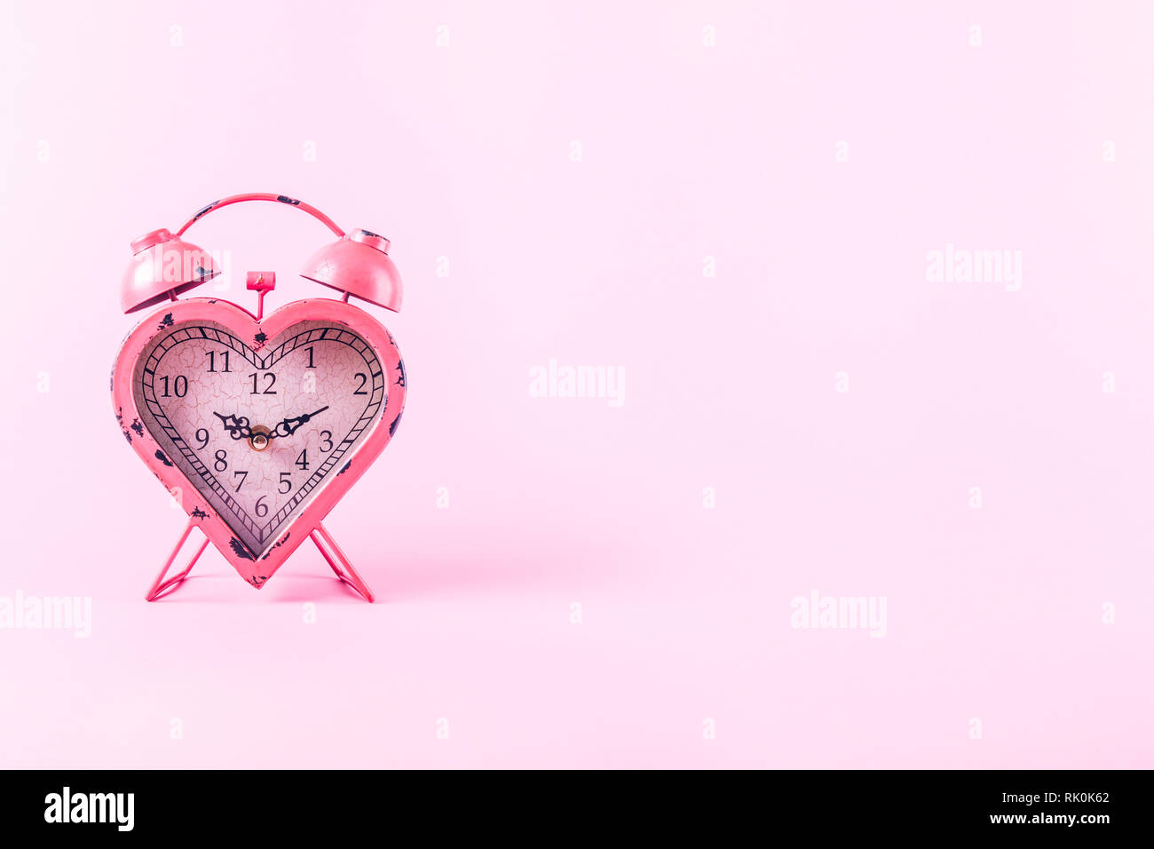 Heart shaped clock on pink background.  Valentines day and love infitity and duration concept. Horizontal - Stock Image