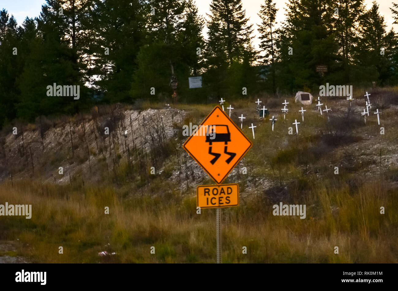Slippery road sign with crosses on the hill behind - Stock Image