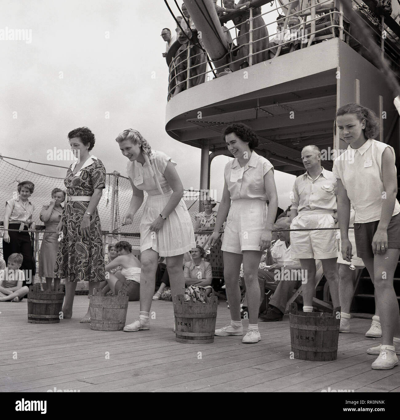 1950s, historical, female passengers with small wooden barrels beside them taking part a deck game onboard a Union-Caste steamship. - Stock Image