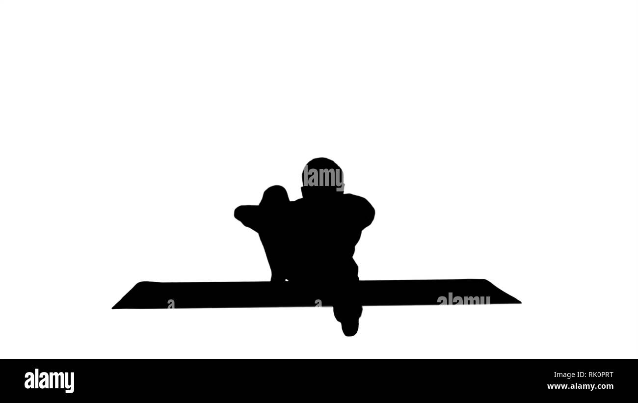 Silhouette Man in Seated Marichyasana yoga pose stretching leg and spine exercise. Stock Photo