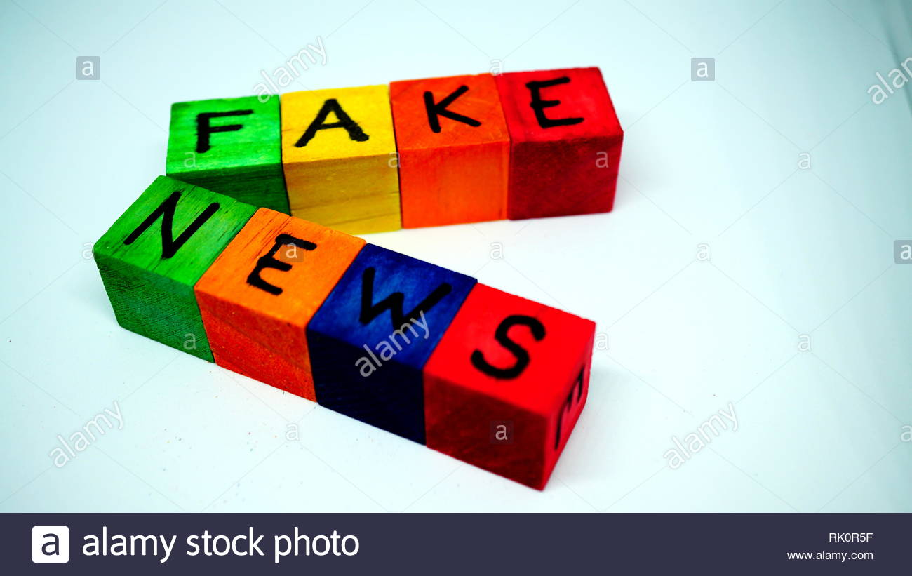 Wooden cubes of rainbow colors with letters form the words FAKE NEWS. White background - Stock Image