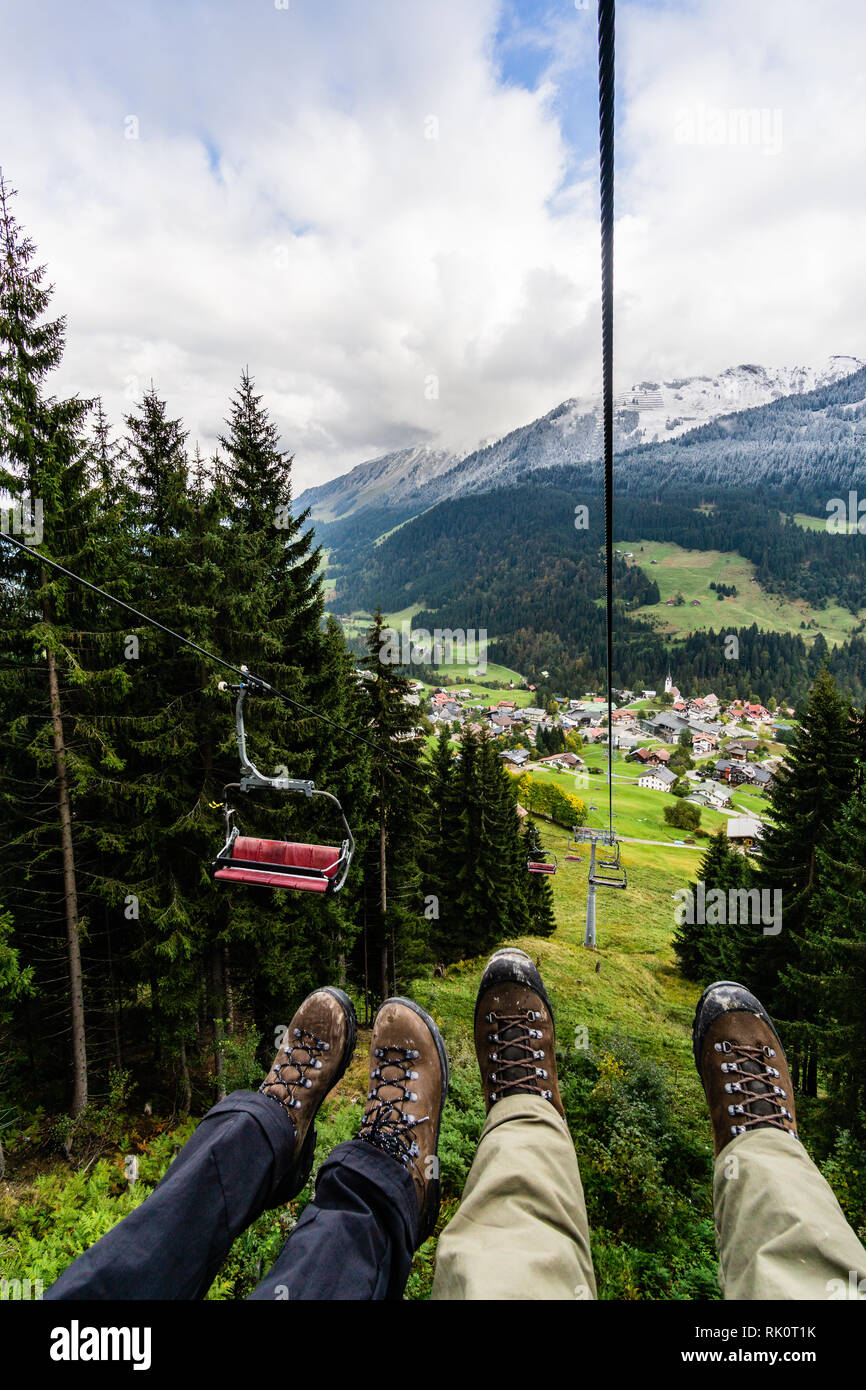 Leg raises skiers on chairlift at ski lift up the high mountain alps germany - Stock Image