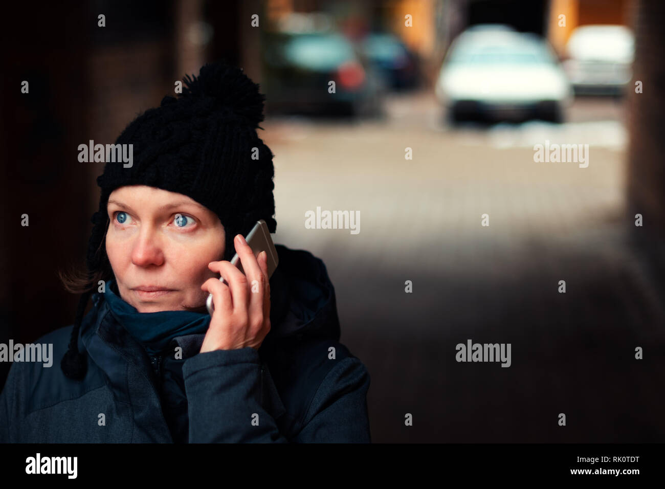Concerned worried woman talking on mobile phone on street on cold winter day Stock Photo