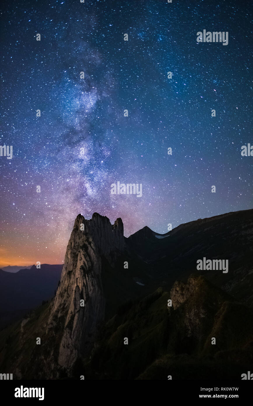 Mountain landscape in the Swiss Alps with jagged peaks and a pristine blue mountain lake in the valley far below. Amazing milky way picture in the swi - Stock Image