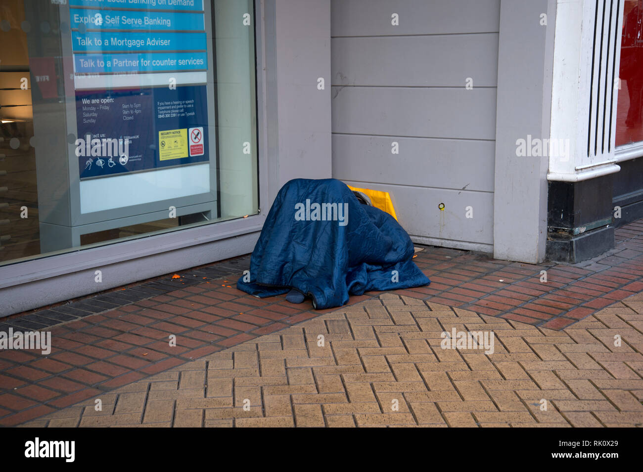 England. Essex. Chelmsford. A rough sleeper outside the TSB bank - Stock Image