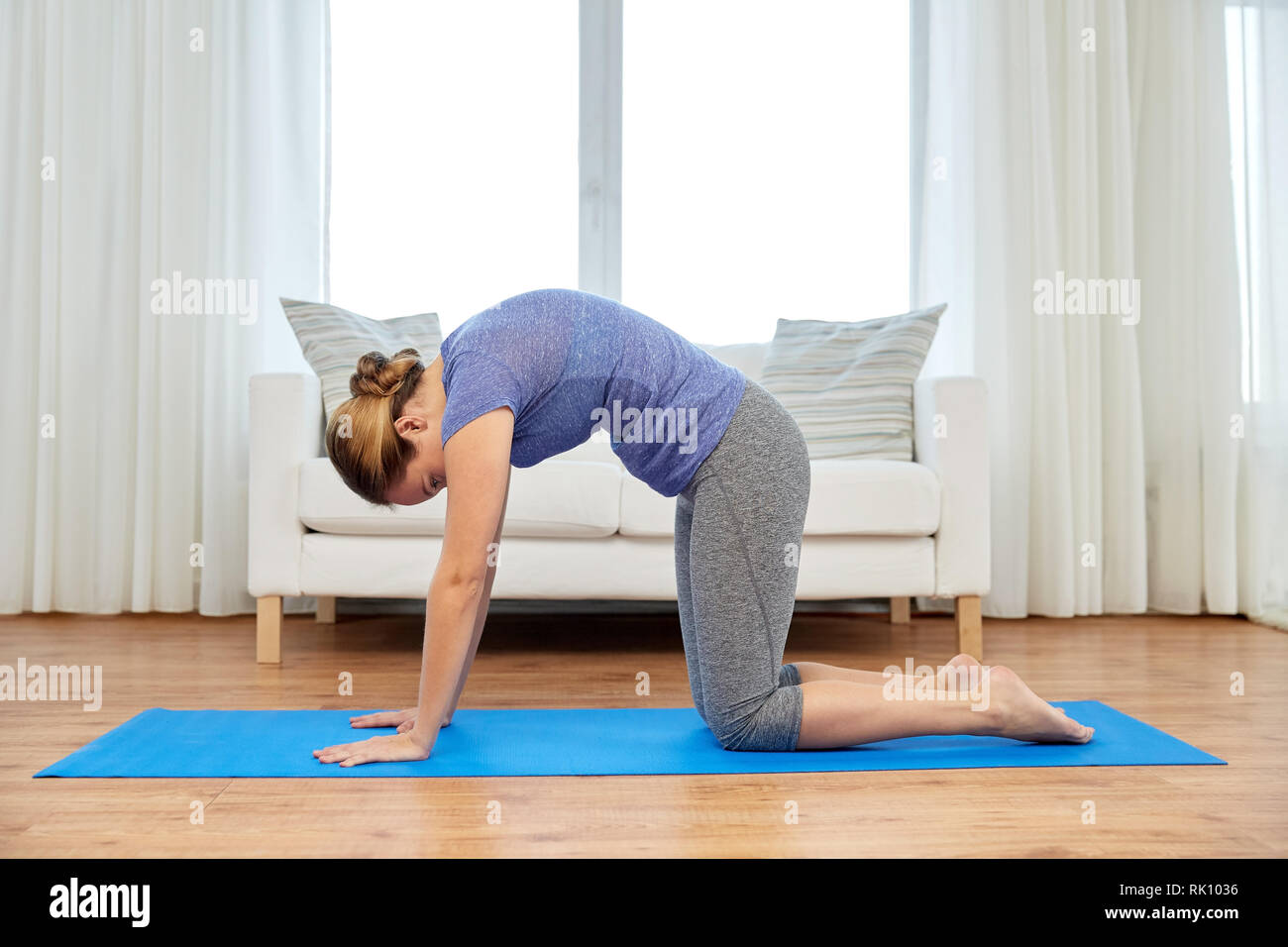 woman doing yoga cat pose at home - Stock Image