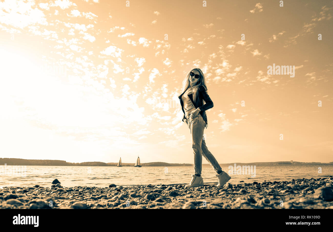Blonde girl with long hair on a photo shoot by the sea - Stock Image