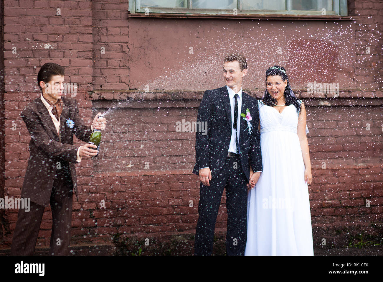 A witness at the wedding opened champagne with splashes - Stock Image
