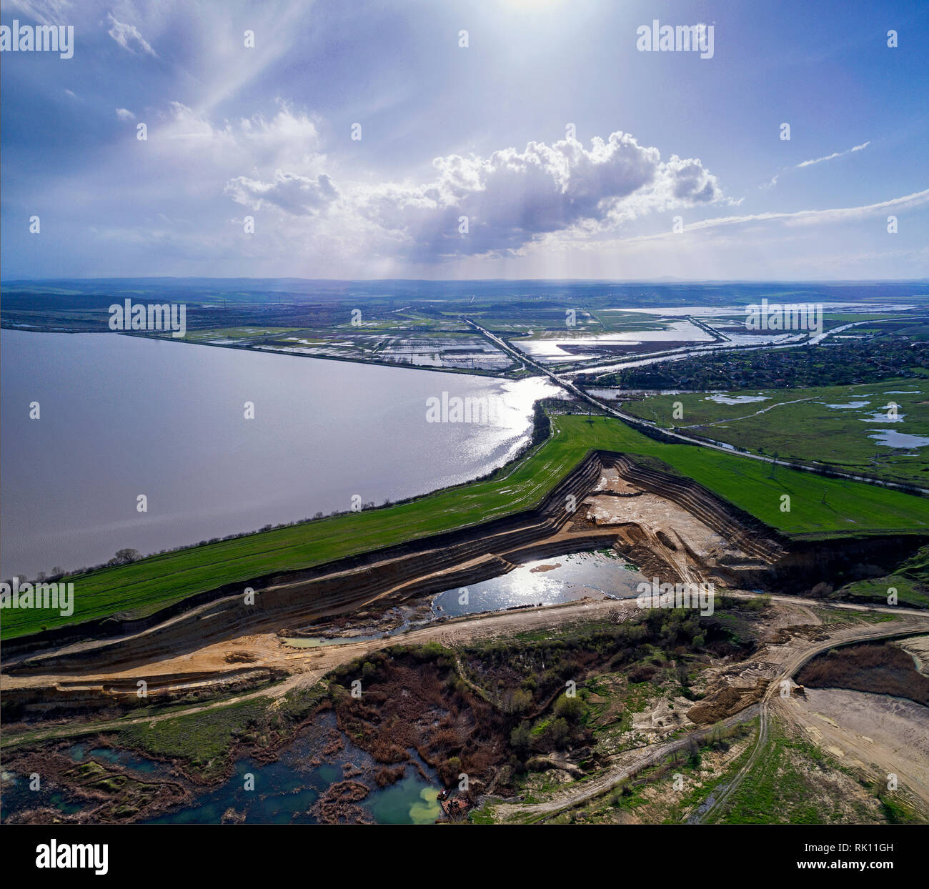 Panoramic view of sand quarry, mining of yellow construction sand, pumping sand with help of powerful pumps, post-apocalyptic landscape - Stock Image