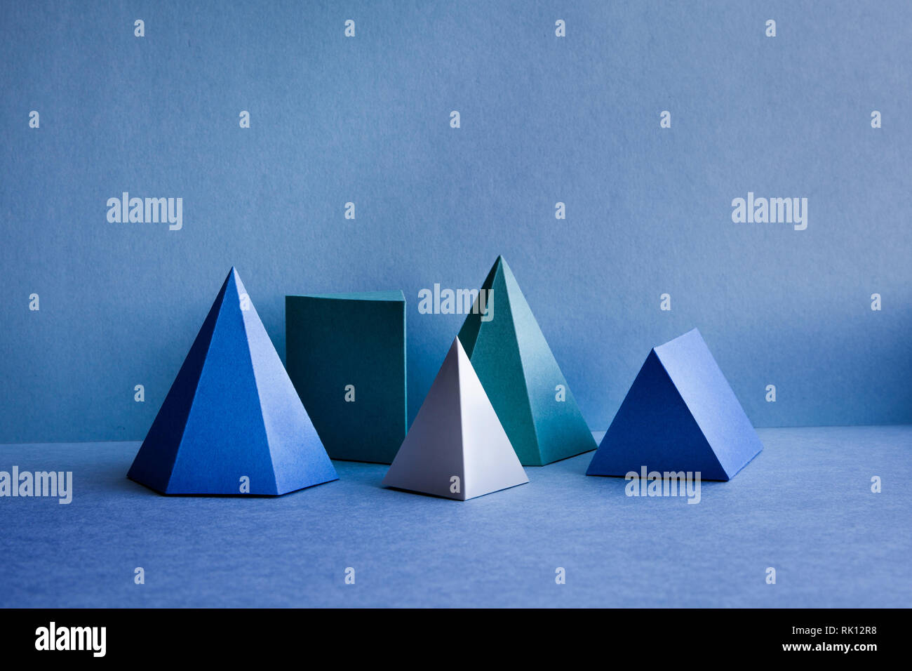 Geometrical figures still life composition. Three-dimensional prism pyramid tetrahedron rectangular objects on blue background. Platonic solids - Stock Image