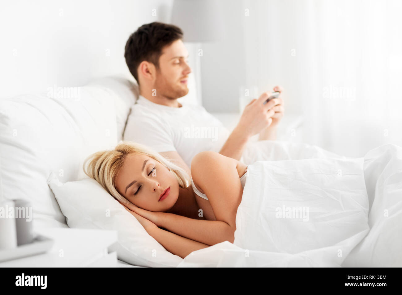 man using smartphone while woman is sleeping - Stock Image