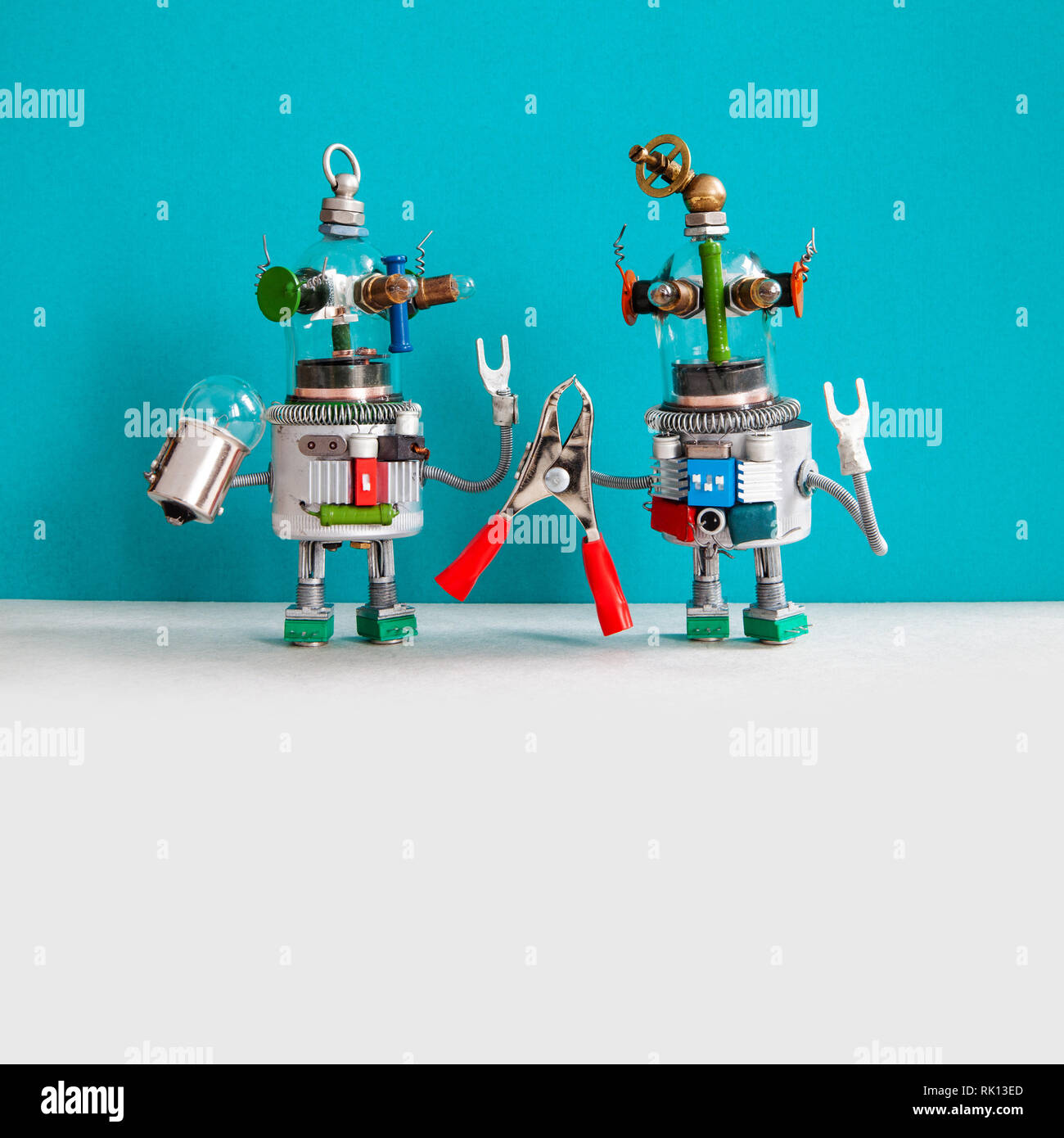 Maintenance repair service concept. Two comical electrician robots are ready for maintenance. Robotic toy handymans red pliers light bulb, blue gray - Stock Image