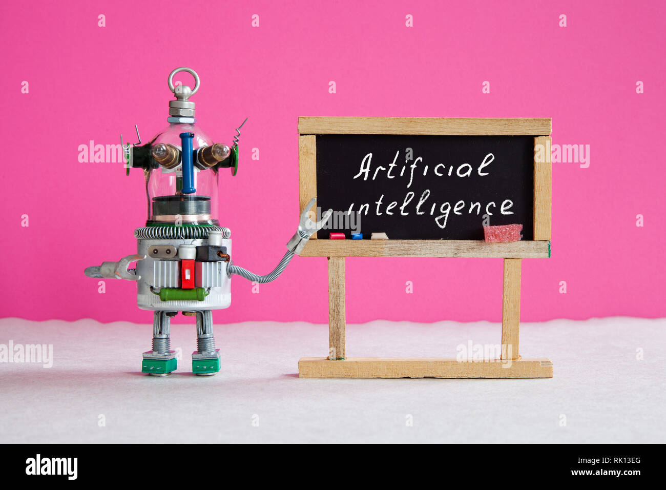 Artificial intelligence and machine learning cocnept. Funny robotic futuristic character, black chalkboard with handwritten text Artificial - Stock Image