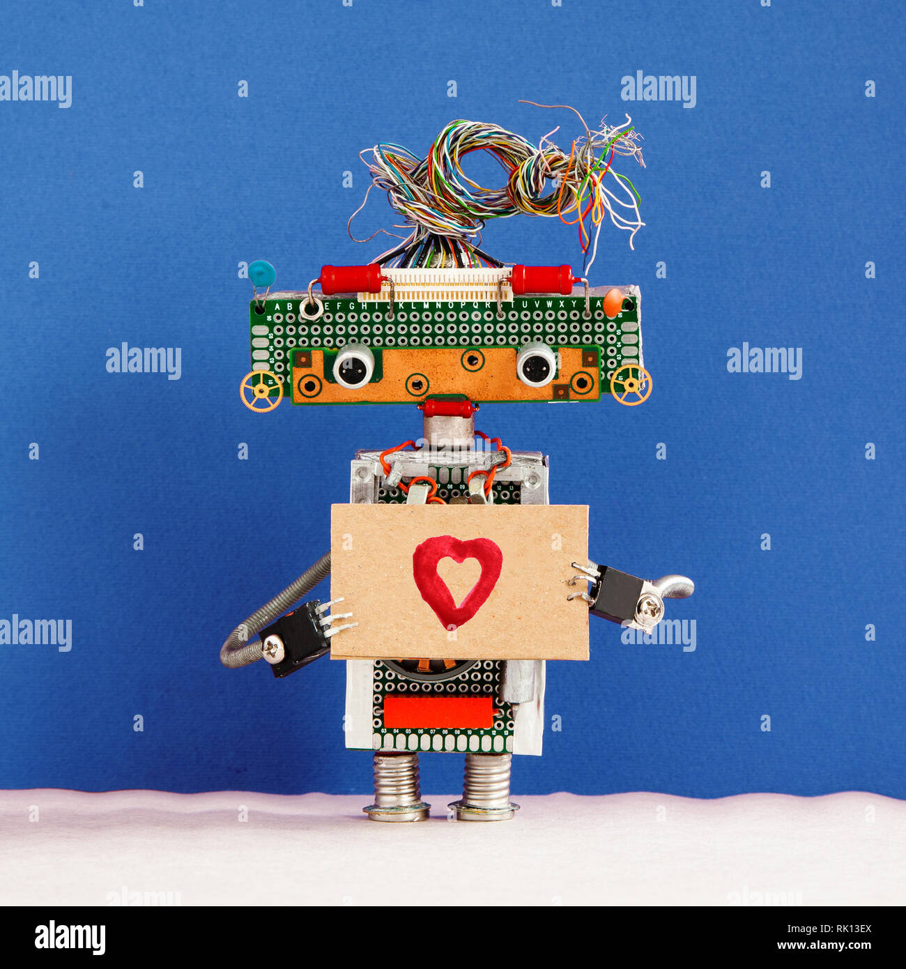 Robot holds greeting card love heart symbol. Valentines day romantic message for all lovers from robotic character. - Stock Image