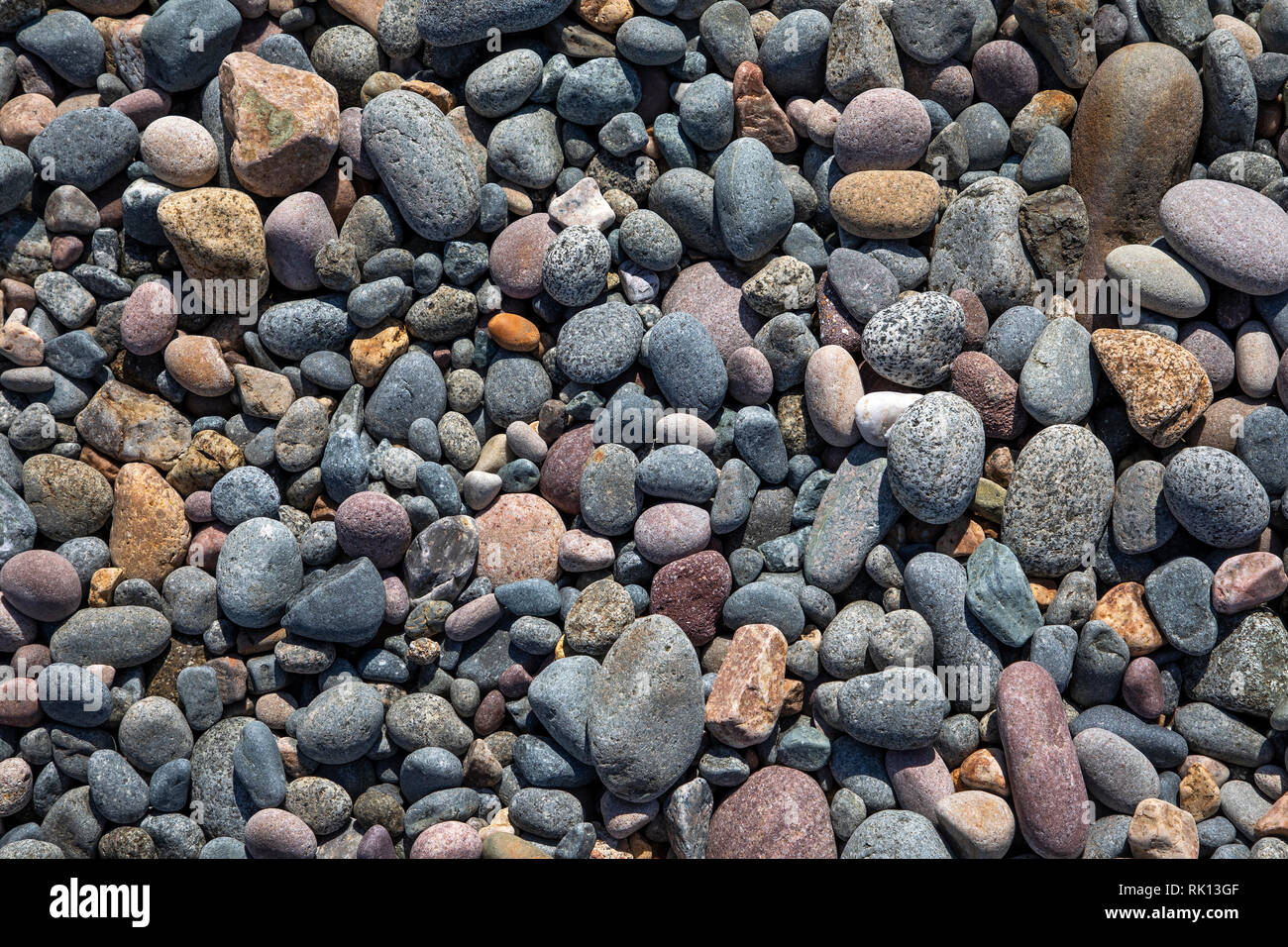 Pebbles on Crabby Bay beach showing the variety of rock types comprising Alderney geology. - Stock Image