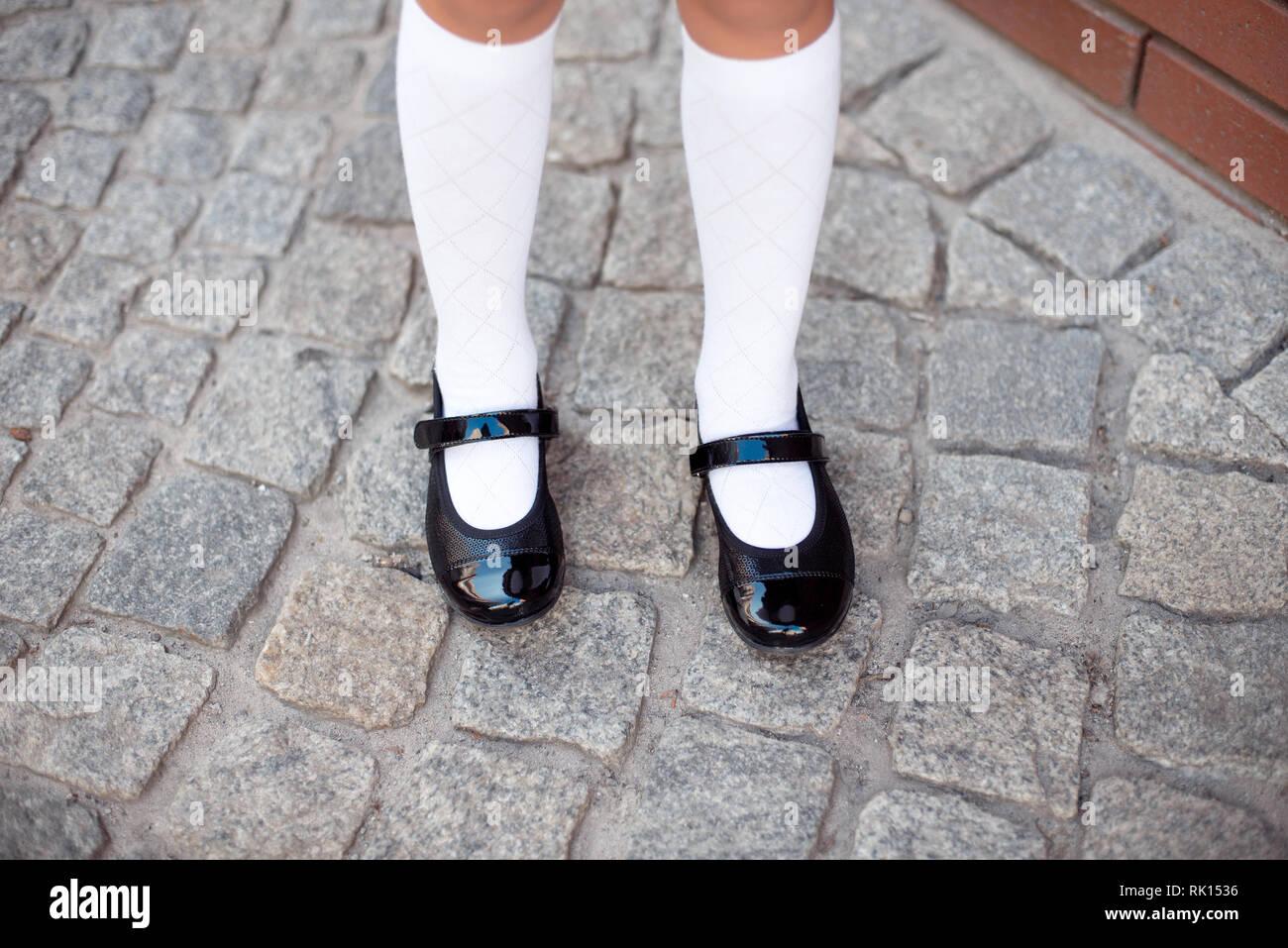 f91d713df4f8 Close-up retro style image of school girl s feet in uniform. - Stock Image