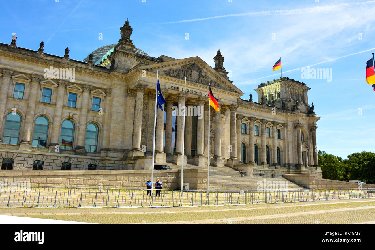 BERLIN, GERMANY - JUNE 21, 2017: German flags waving in the wind at Reichstag building, seat of the German Parliament (Deutscher Bundestag), on a sunn - Stock Image