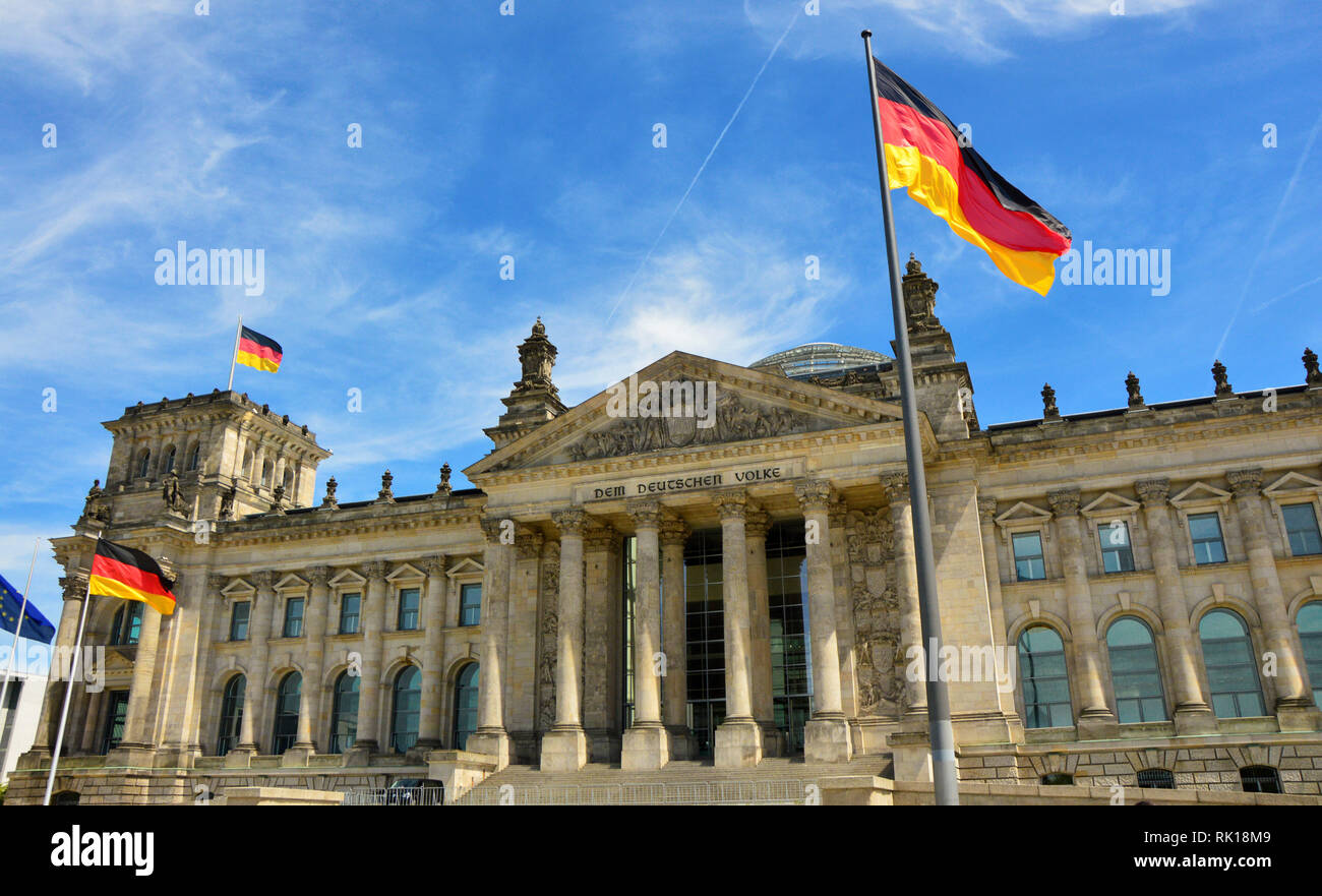 German flags waving in the wind in front of famous Reichstag building, Berlin, Germany - Stock Image