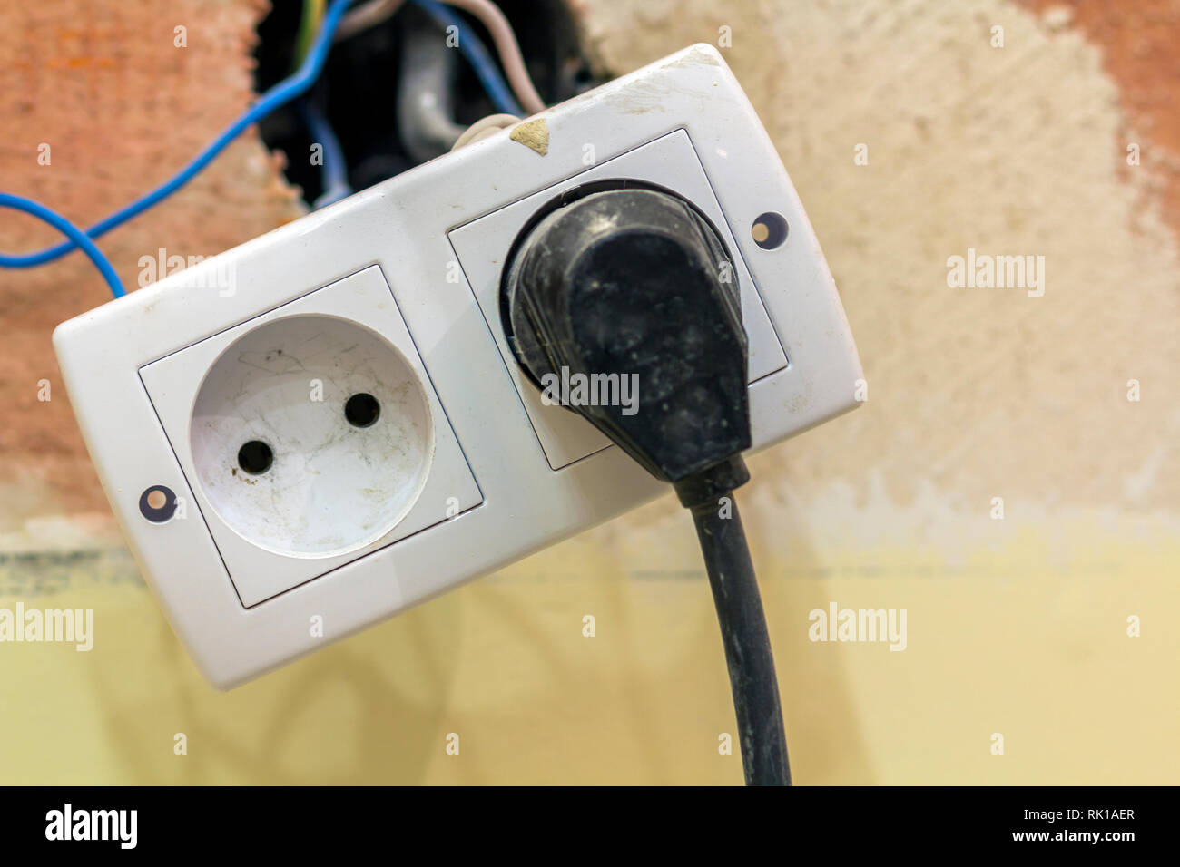 power outlet in double socket with connecting electric isolated colorful  wires, plastic plug installation on light yellow plastered wall  home  interio