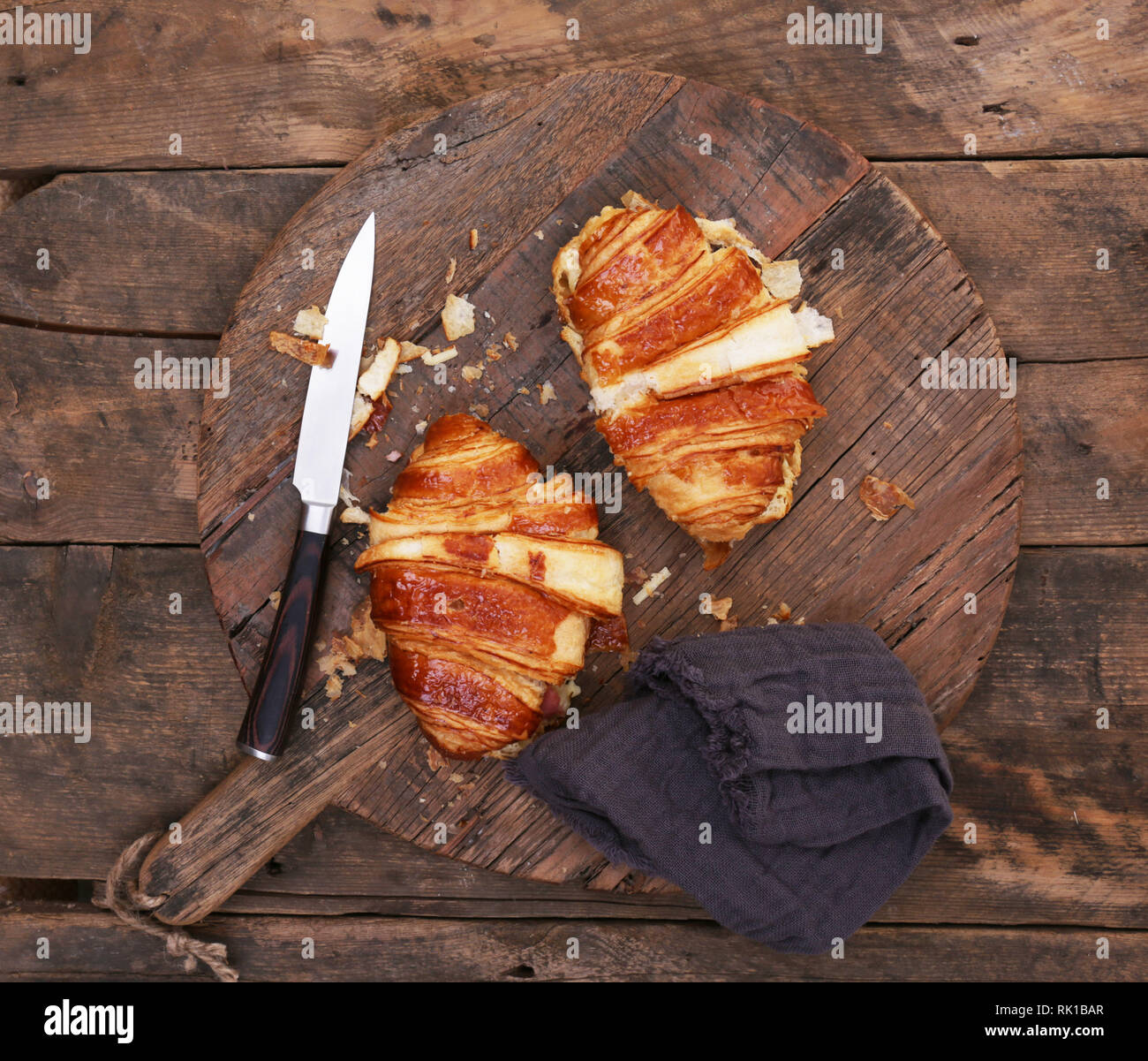 Cheese and bacon croissant on a wooden cutting board with knife - Stock Image