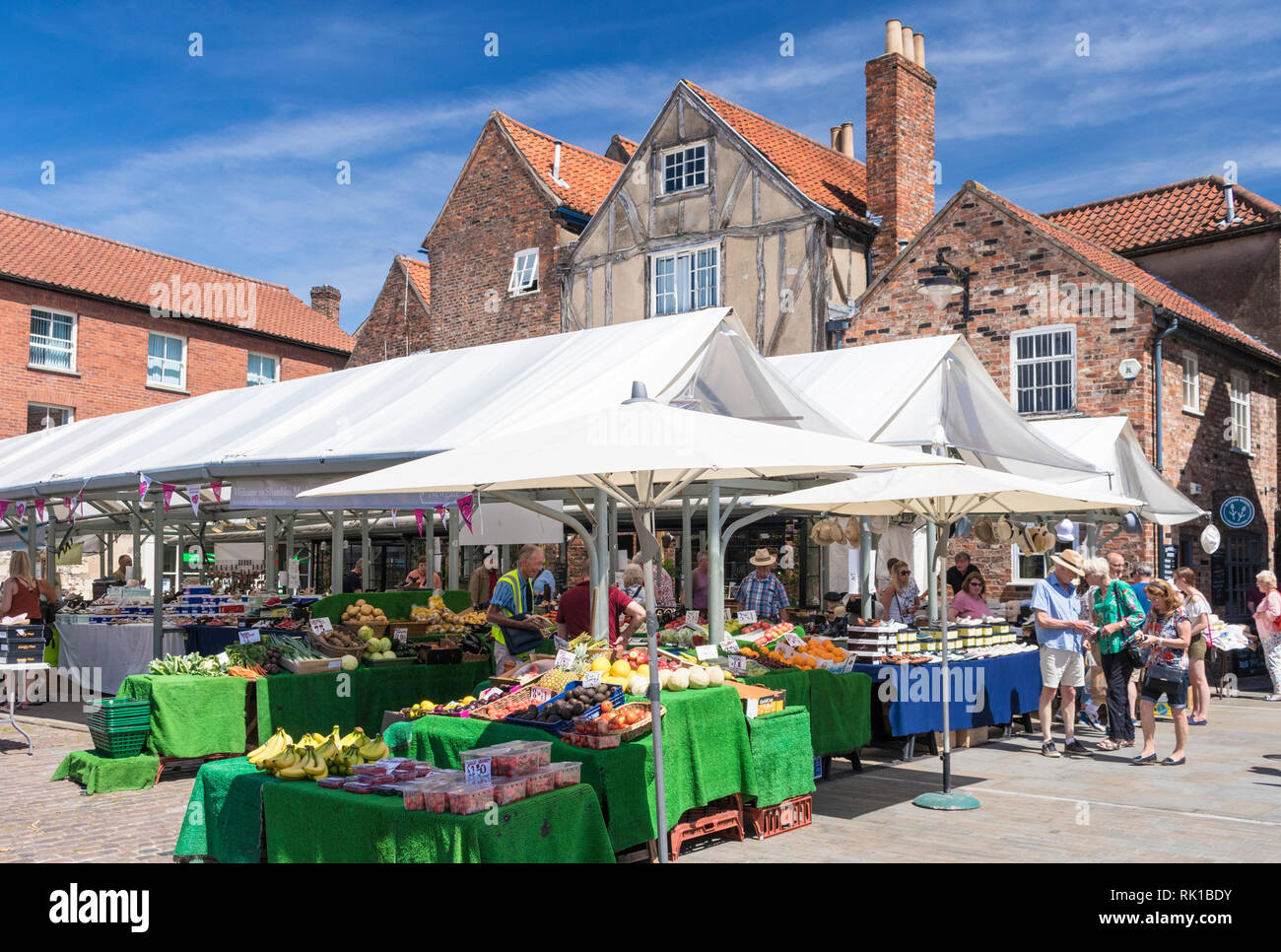 People shopping around a greengrocers fruit and veg stall in the Shambles Market York city centre York  North Yorkshire England GB UK EU Europe - Stock Image