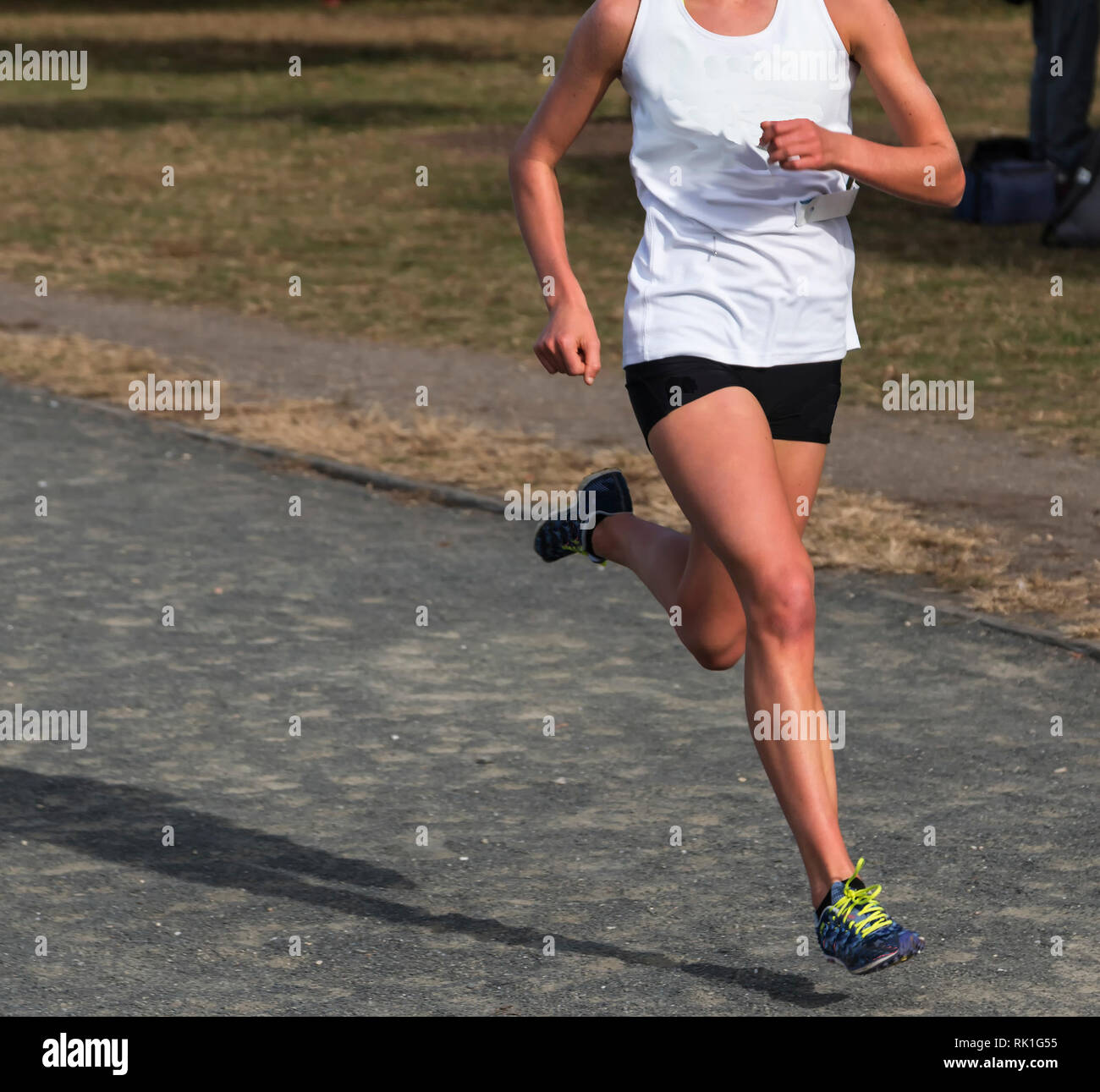 A high school female cross country runner runner racing on a gravel path wearing a white top and black pants, outsie on a sunny fall afternoon. - Stock Image