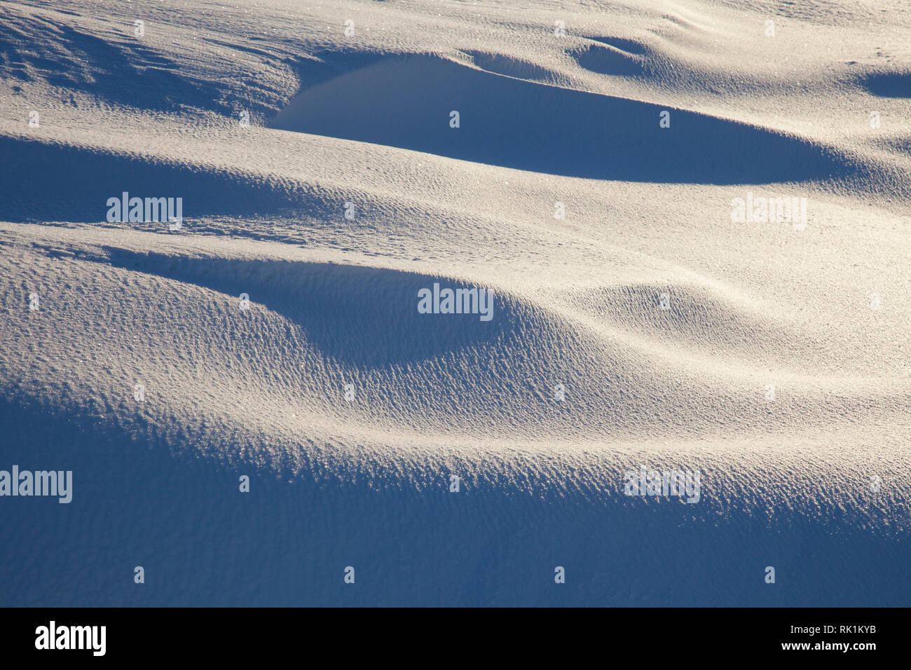 Thick irregular snow layer / snow cover shaped by strong wind - Stock Image