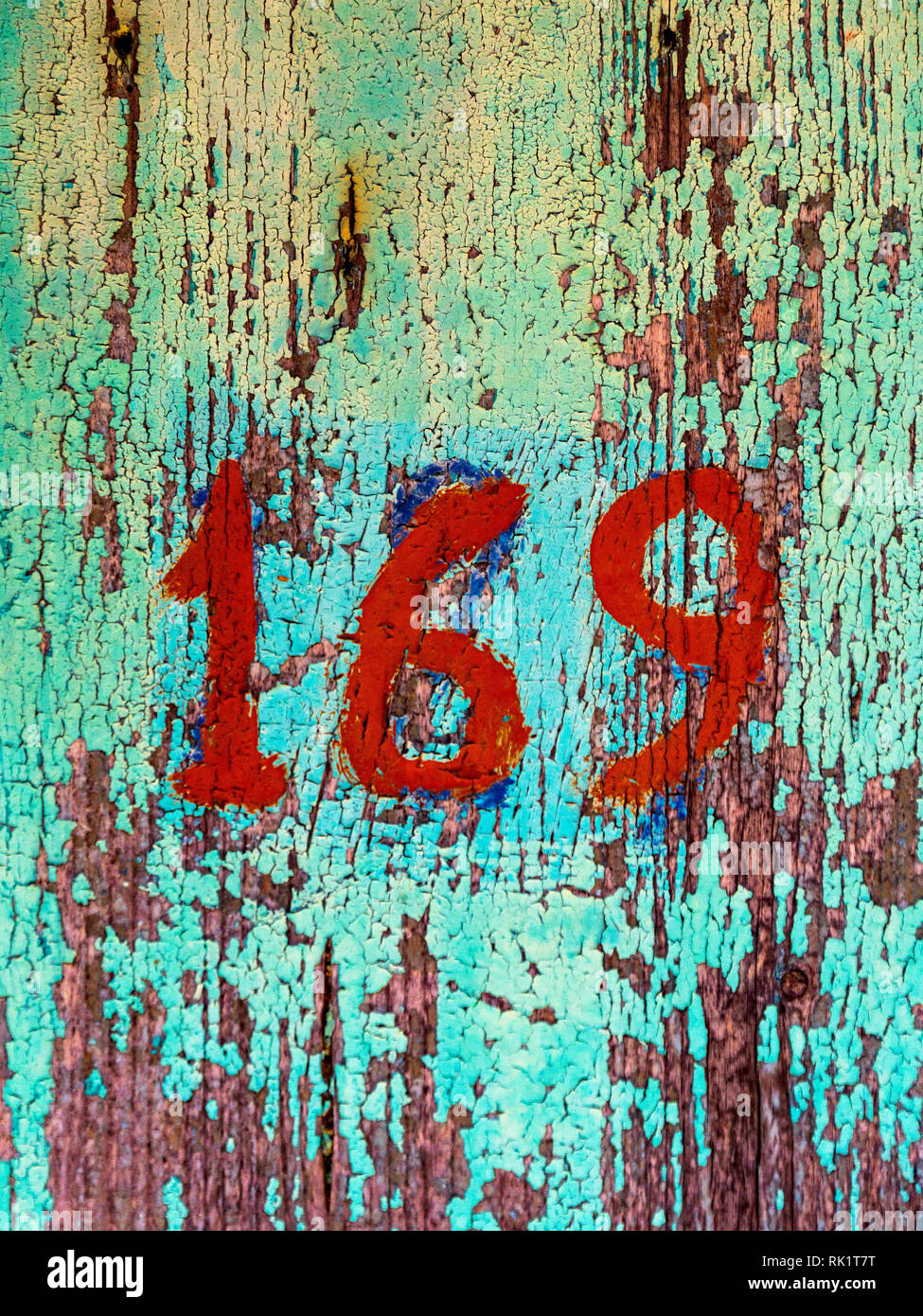 Numer 169 painted on old decayed door - Stock Image