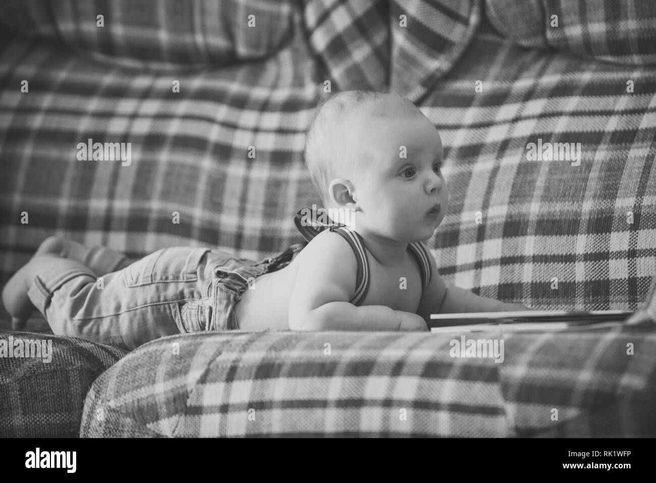 Infant wear jeans and suspenders at home - Stock Image