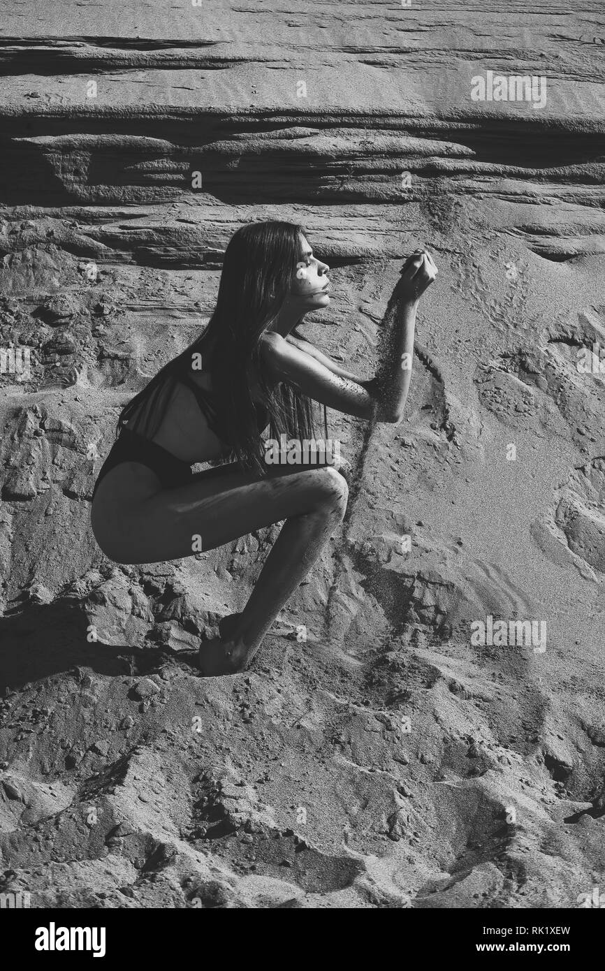 Woman with fit body play with sand, bodycare - Stock Image