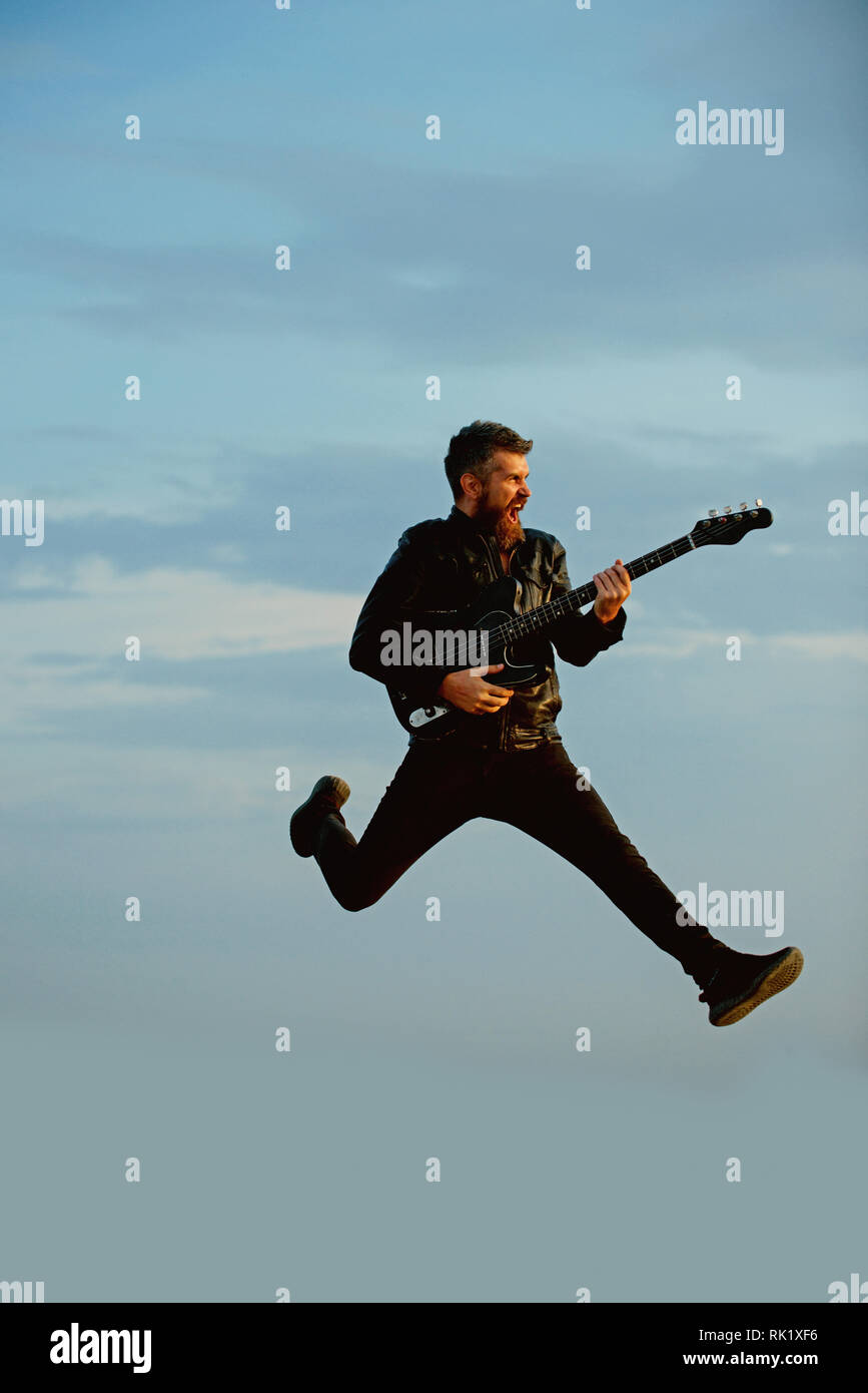 Music is so much fun. Bearded man jump with guitar on blue sky. Hipster guitarist with beard on excited face play in clouds. Like rock star. Feeling - Stock Image