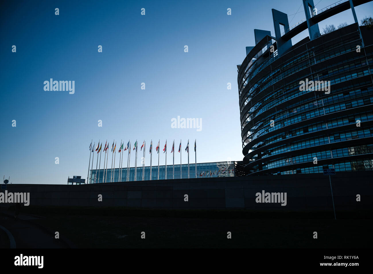 Silhouette of European Parliament building with all EU members state flags waving newsworthy image blue toned image for news - Stock Image