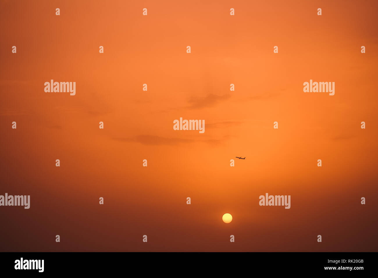 Dark silhouette of airplane in distance in air and sunset sun in background. Plane making take off from airport in Turkey. Horizontal color photograph - Stock Image