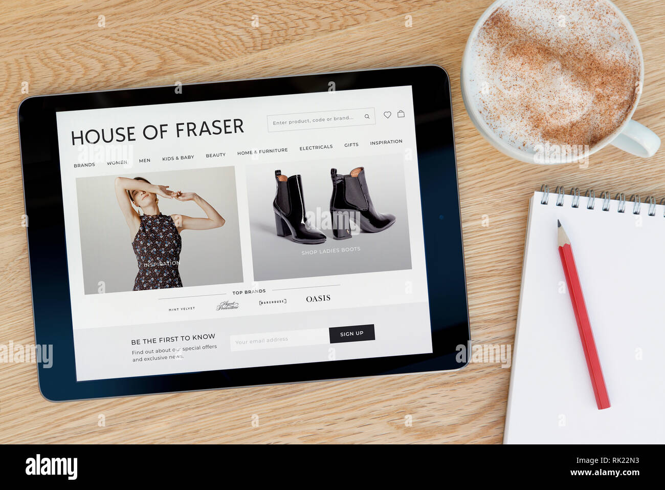 The House of Fraser website features on an iPad tablet device which rests on a wooden table beside a notepad (Editorial use only). - Stock Image