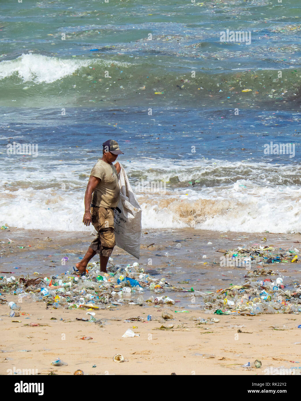 Pollution, lone man picking up plastic bottles, cups, straws and other litter washed up on the beach at Jimbaran Bay, Bali Indonesia.. - Stock Image