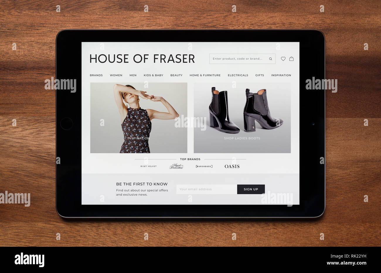 The website of House of Fraser is seen on an iPad tablet, which is resting on a wooden table (Editorial use only). - Stock Image