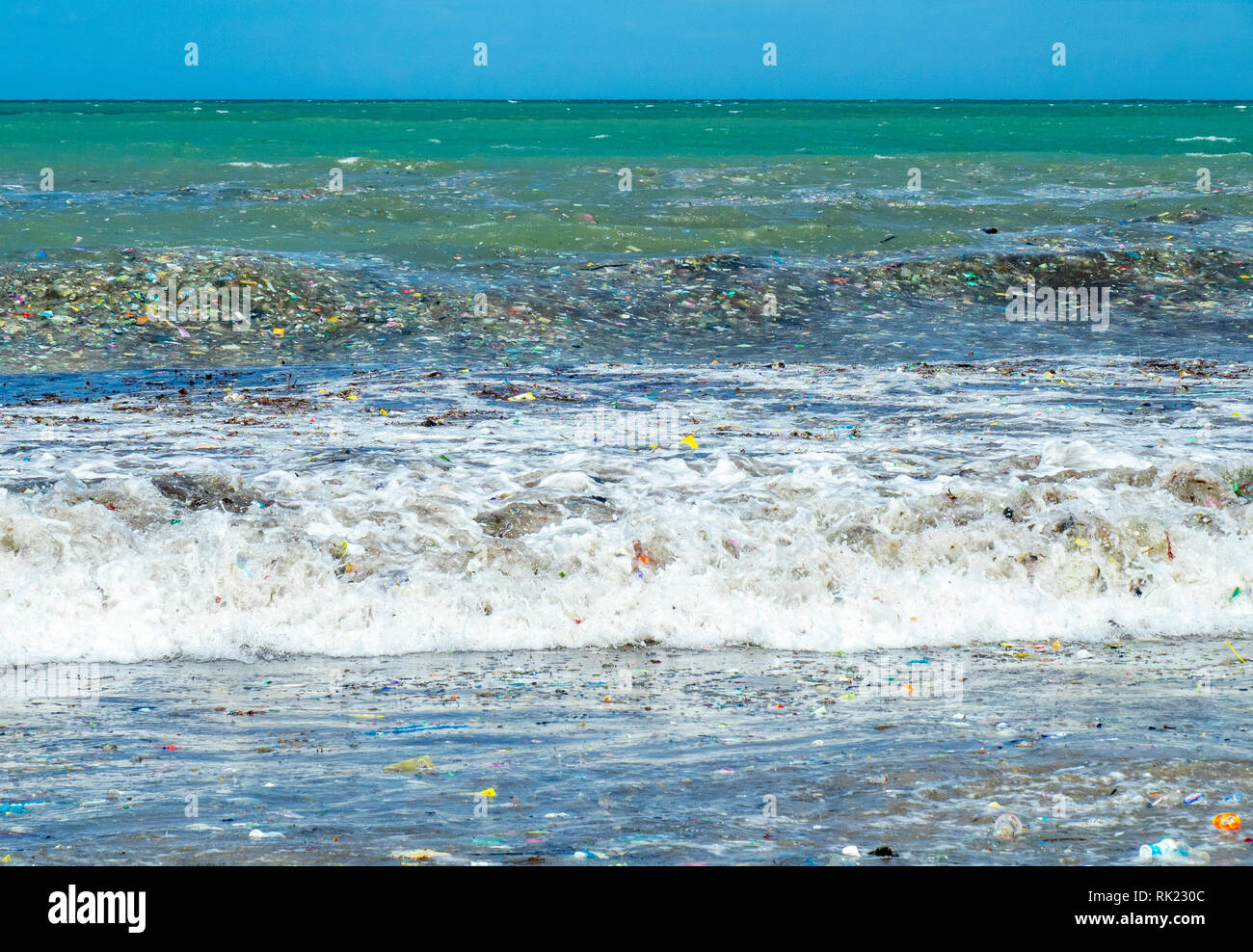 Pollution of plastic bottles, cups, straws and other litter washing up on the beach at Jimbaran Bay, Bali Indonesia. - Stock Image