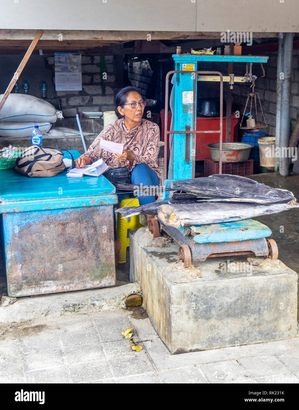 Woman weighing  a large piece of dried fish on scales in Jimbaran, Bali Indonesia. - Stock Image