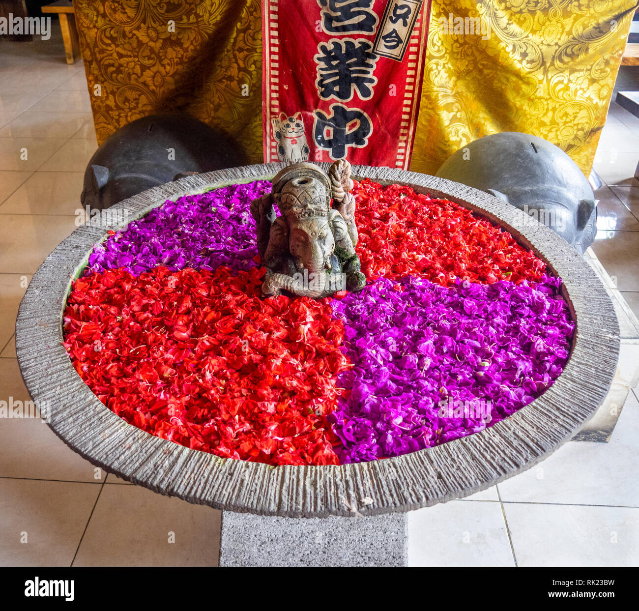 An urn filled with red and magenta flower petals in Jimbaran, Bali Indonesia. - Stock Image