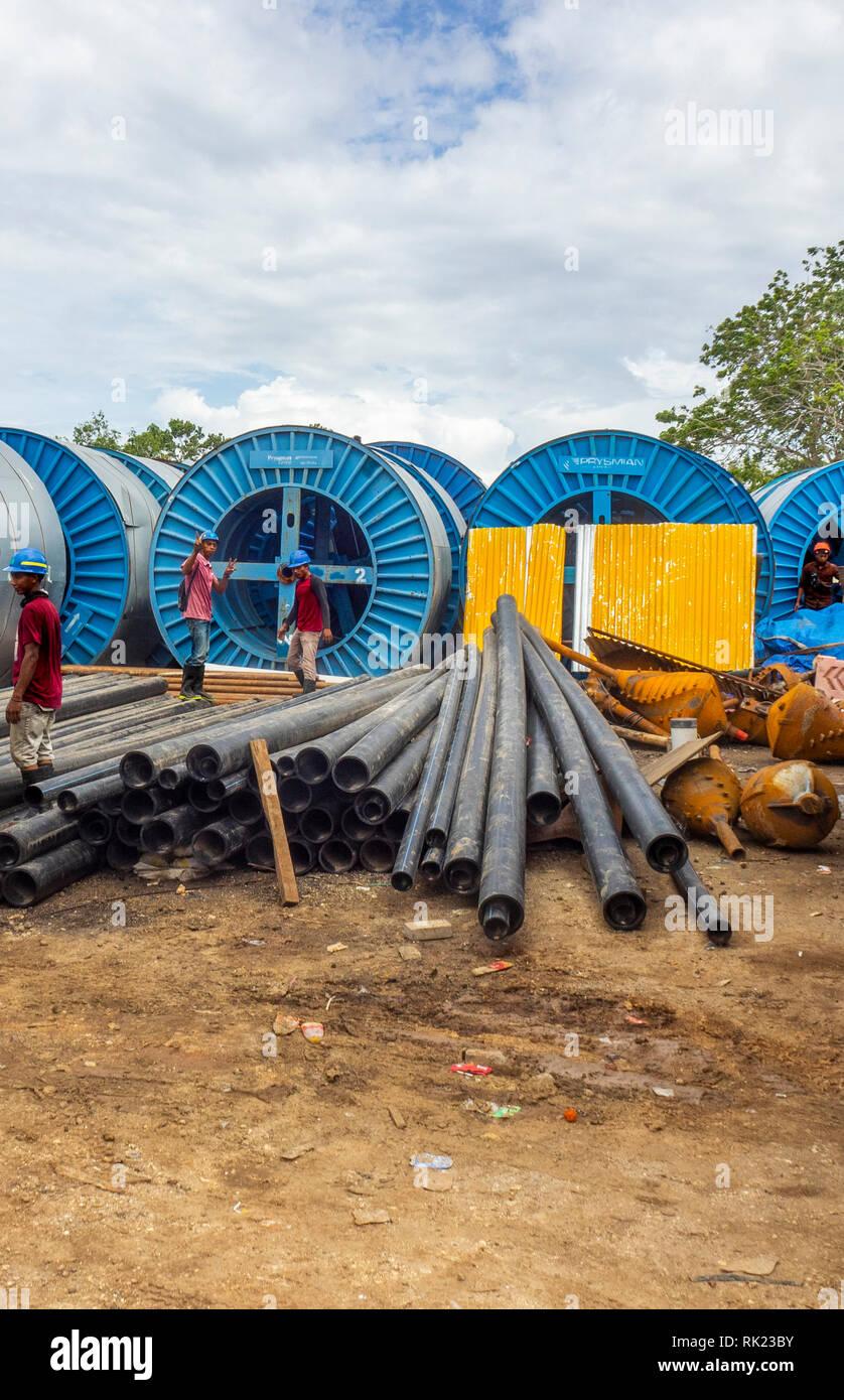 Workmen in a yard full of pipes in Jimbaran, Bali Indonesia. - Stock Image